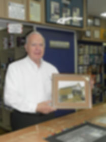 Strothkamp's Paint Center owner Bob Strothkamp holding picture of original Strothkamp's Paint Center store circa 1956