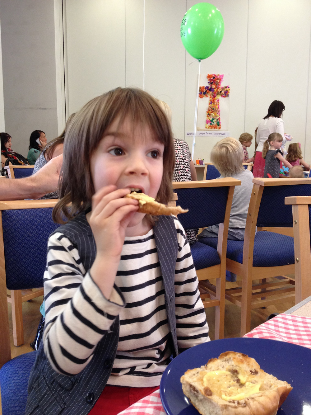 Child eating hot cross bun
