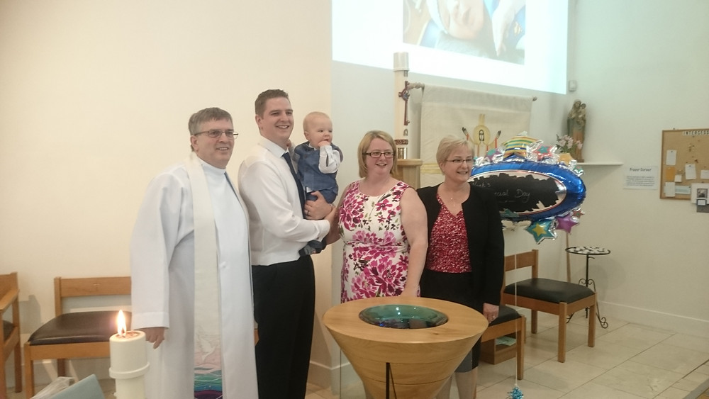 Rev Malcolm Hendry and his family at the font