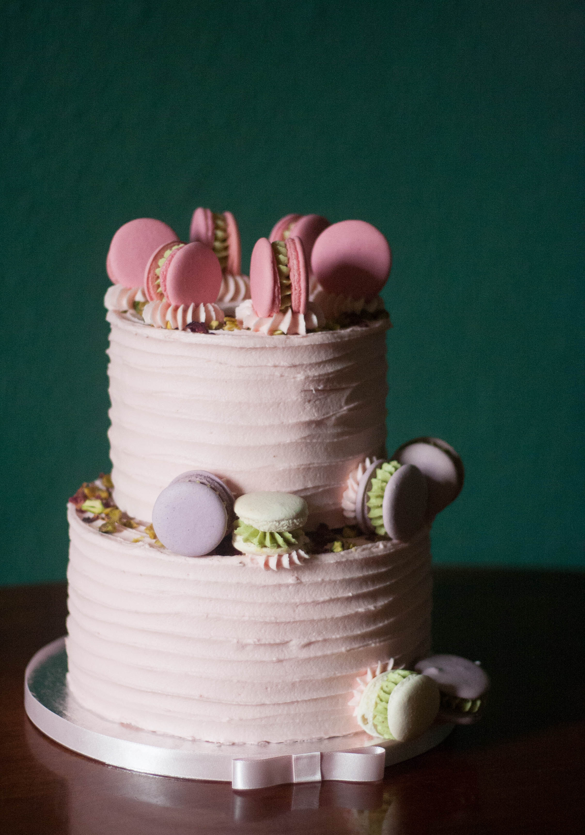 two tier pink frosted wedding cake rose pistachio vegan