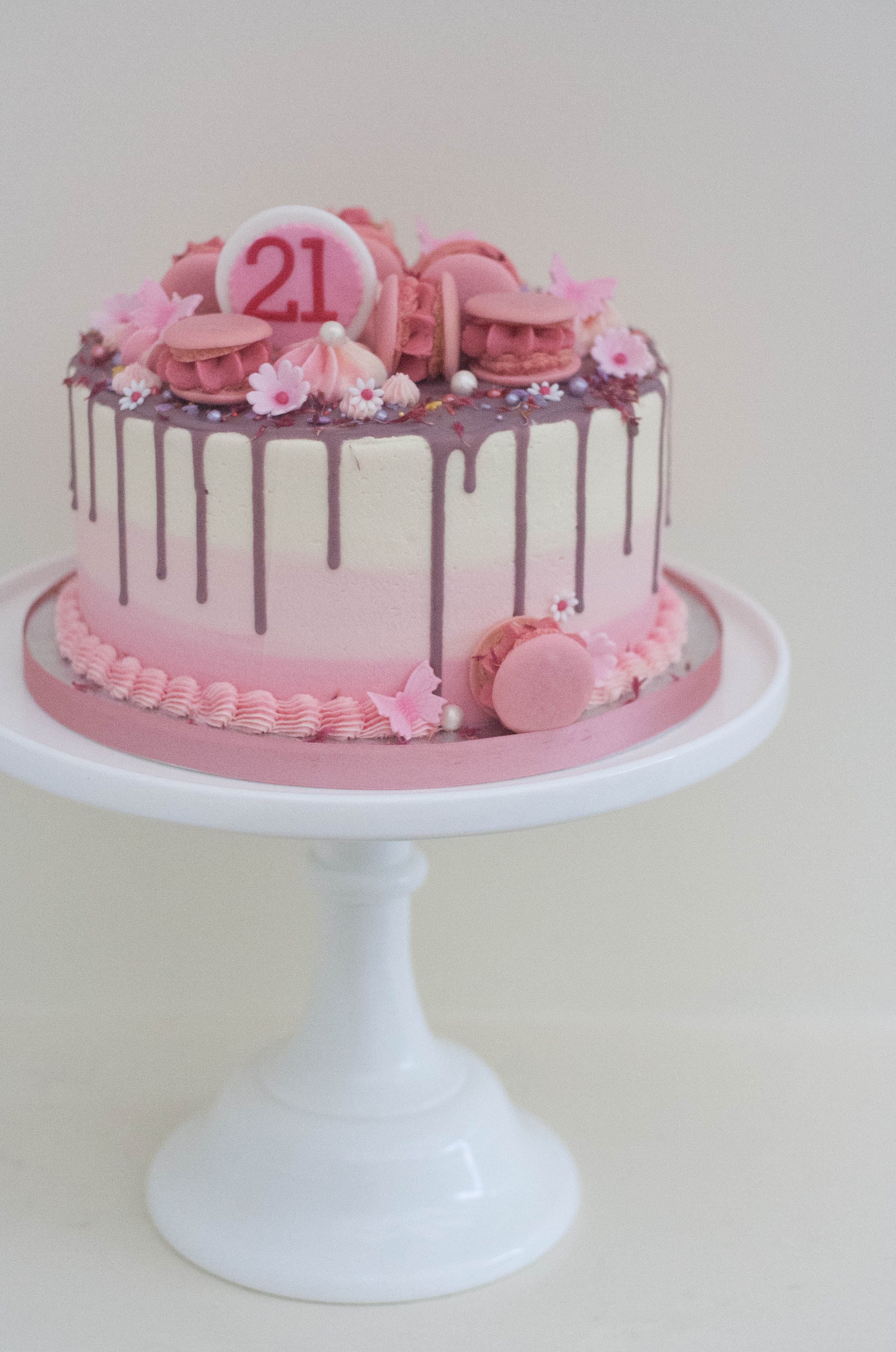 pink ombre drip cake with macarons sprin