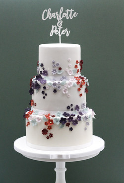 three tier blossom wedding cake with white names topper