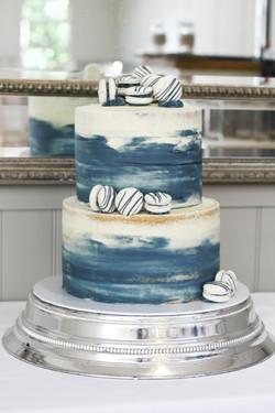 navy semi naked wedding cake with macarons