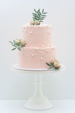 two tier blush pink frosted cake with pe