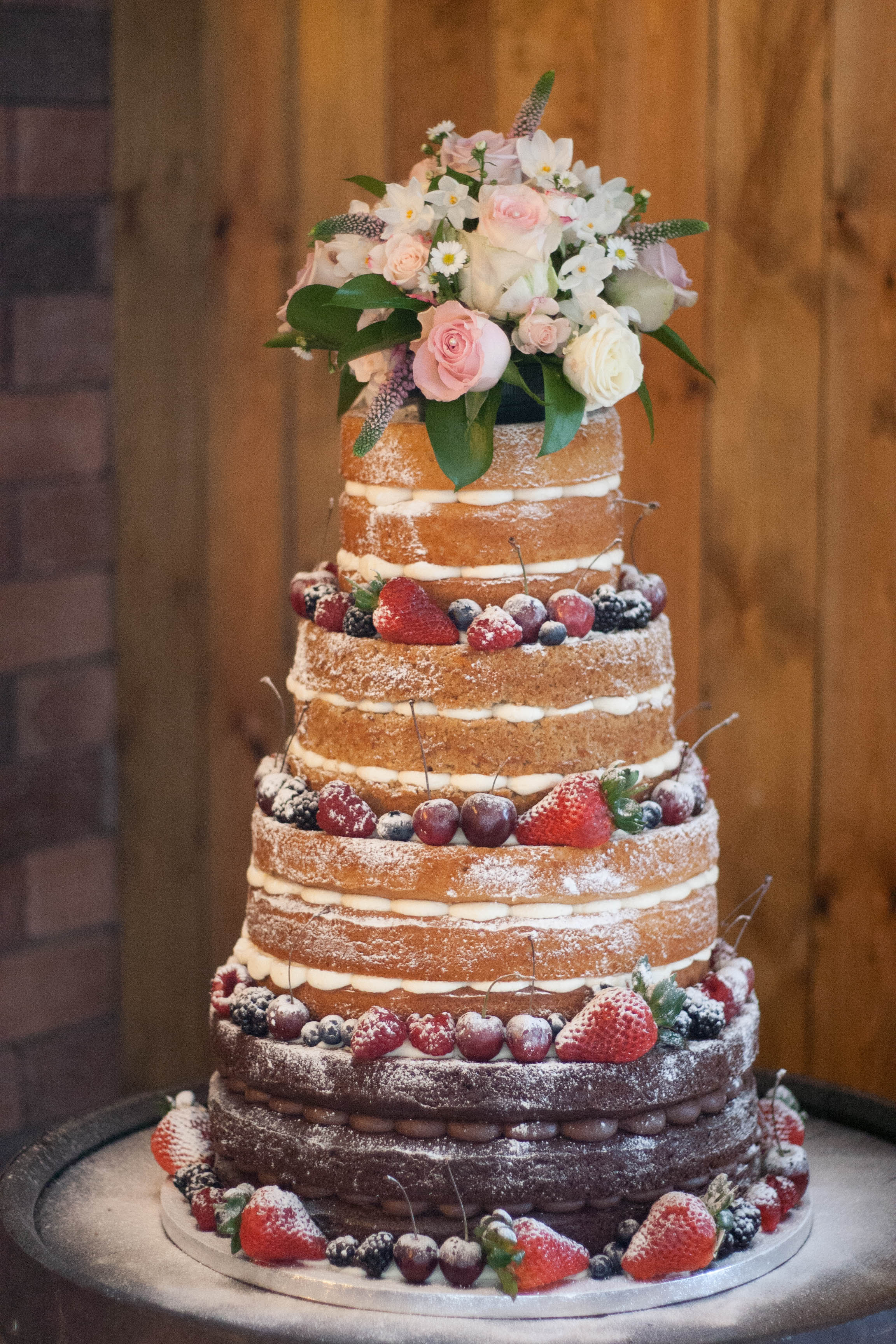 naked wedding cake four tier fresh flowers vegan