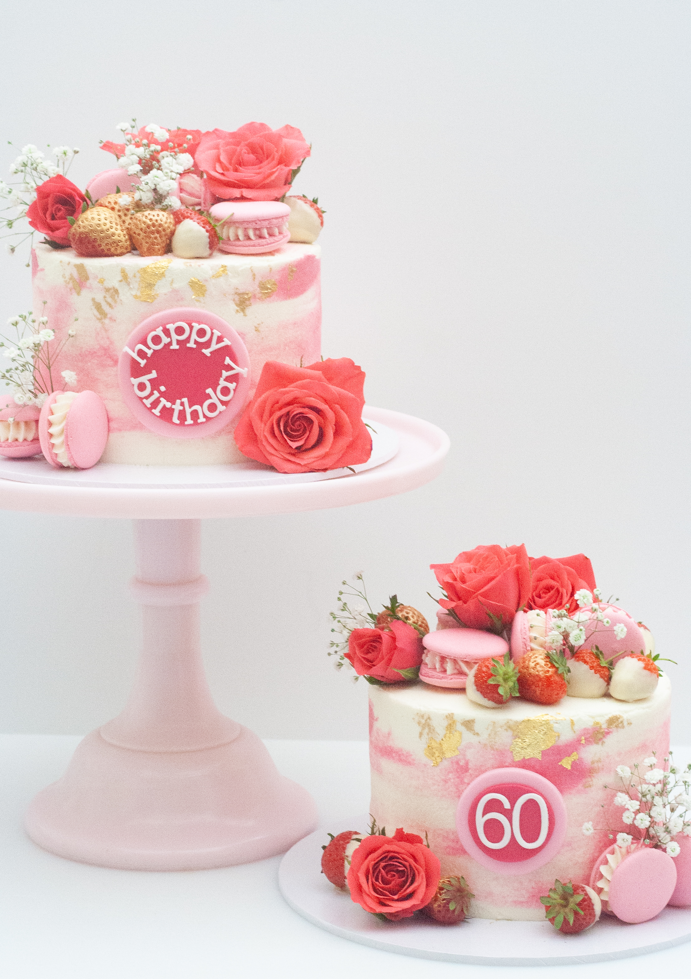 two pink watercolour cakes with strawber