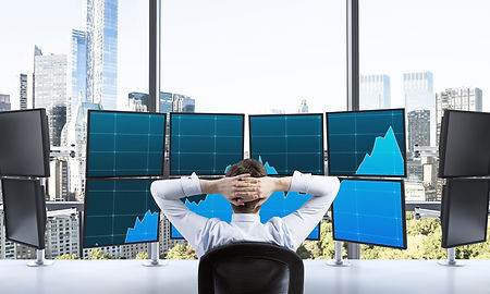 Financial Trader in front of screens