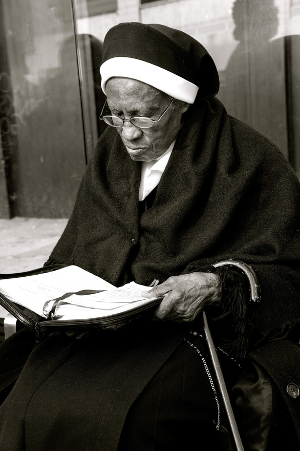CLERGY WOMAN AT BUS STOP IN HARLEM