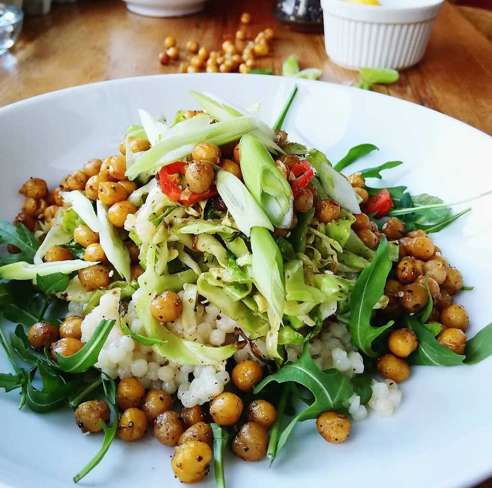 Giant couscous salad served warm with crispy chickpeas, sweetheart cabbage and zataar