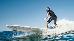 young-man-surfs-ocean-waves.jpg