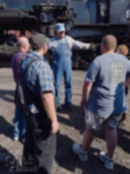 Strasburg Rail Road fireman Earl Knoob talking to the hosting tour group