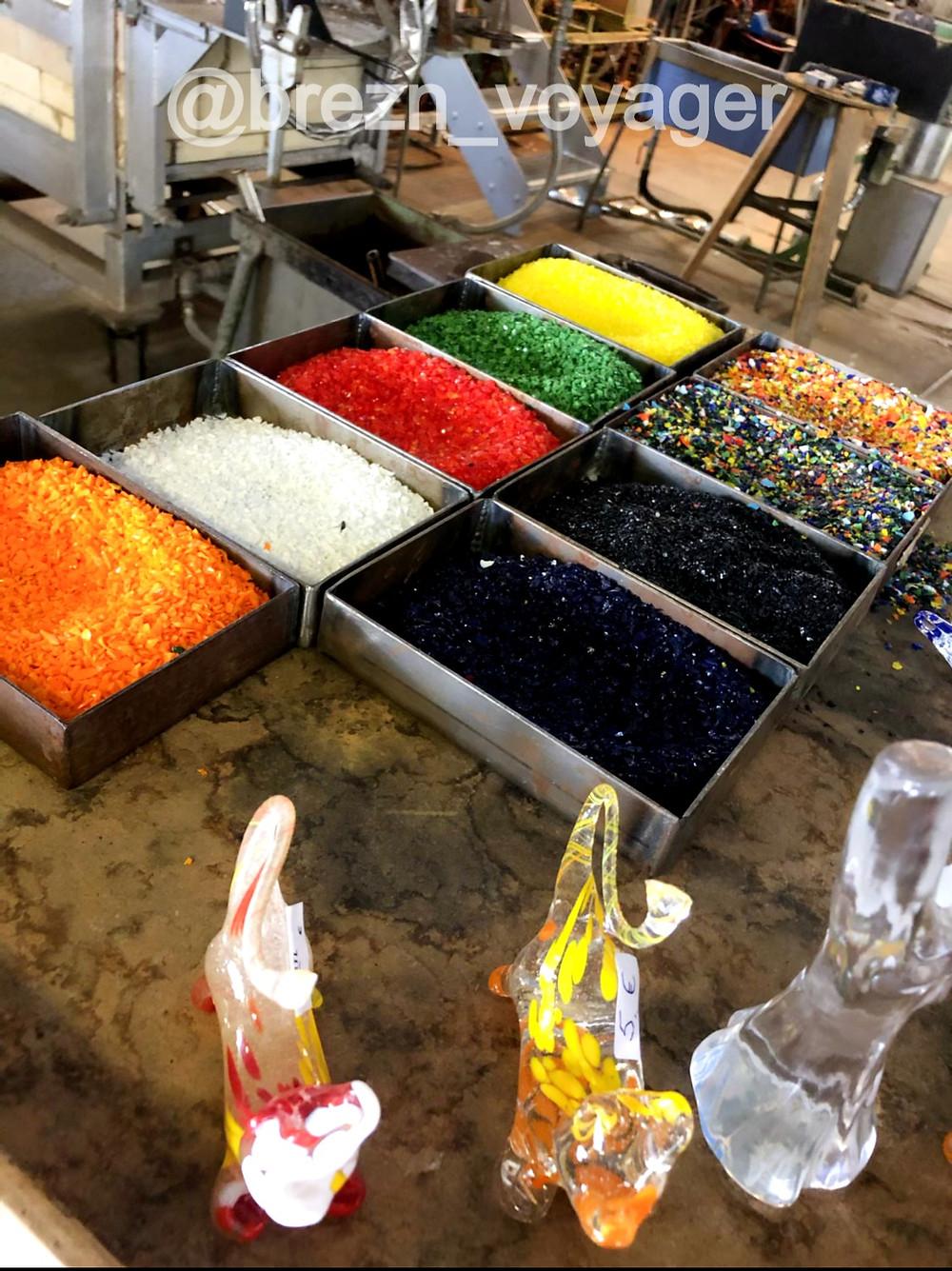 Mit Hilfe von bunten Glassplittern kann der Glasbläser seine Werke einfärben. Hierzu taucht er den heißen Glaskolben in die Farben und bring dies wieder in den Ofen um die Splitter zu schmelzen