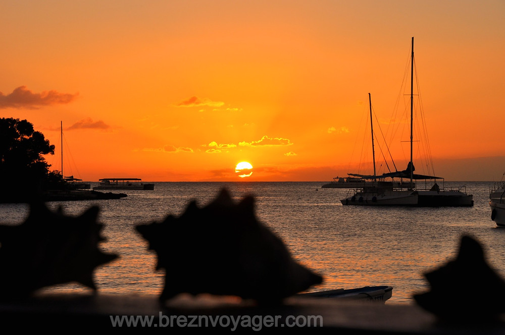 Die Sonne geht auf der Dominikanischen Republik im Wasser unter. Die Boote treiben im Hafen von Bayahibe