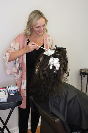 Knowledgeable Indigo Collective hair stylist performing hair color services for client in Lebanon