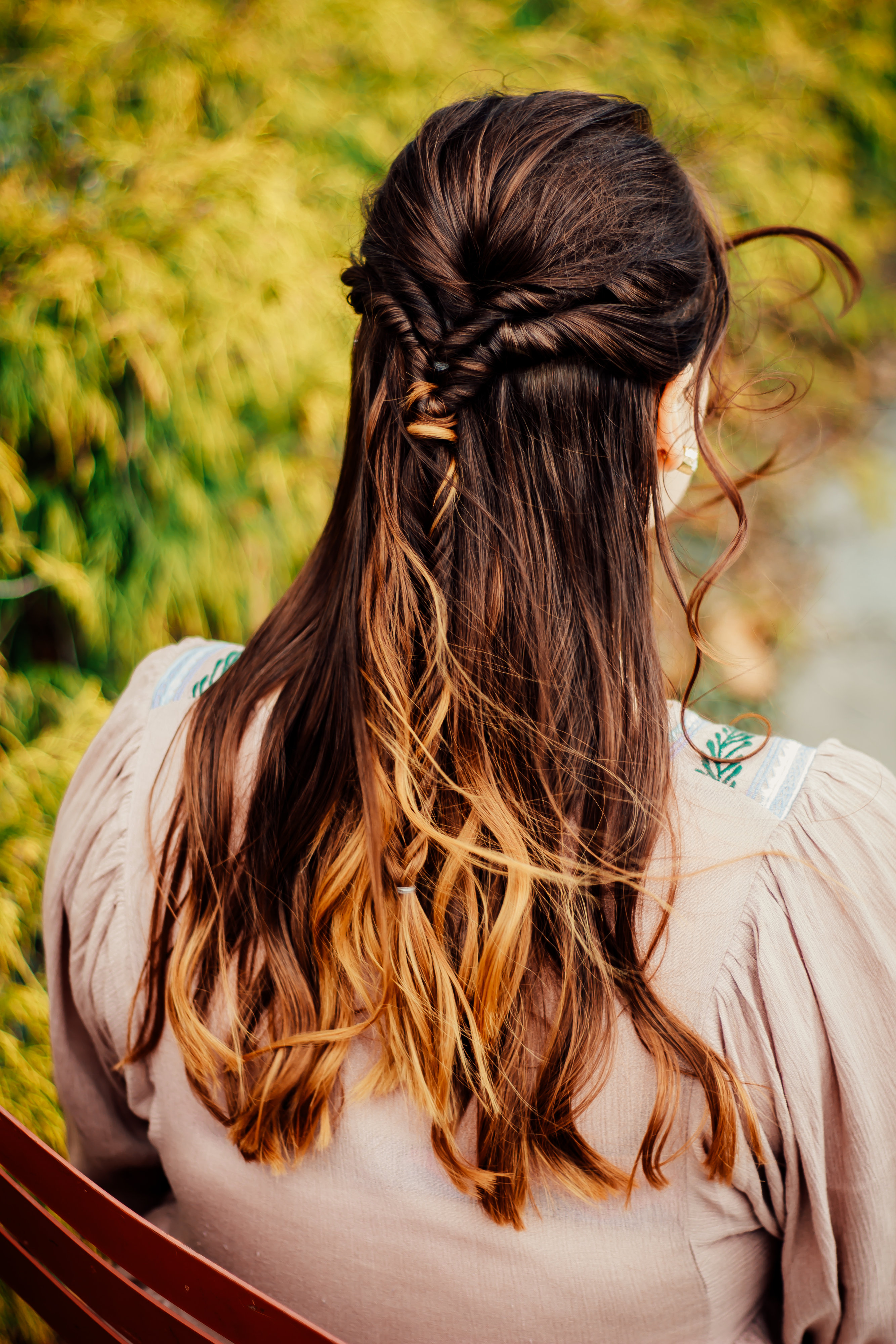 Woman with braided two-tone half-do, colored & styled by Indigo Collective hair stylist in Lebanon
