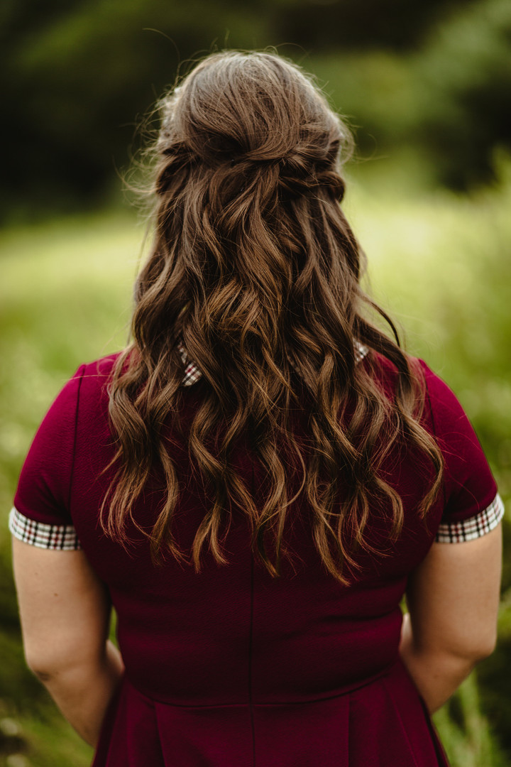 Brown hair curled and put up into half-do by Indigo Collective hair stylist team near Clinton