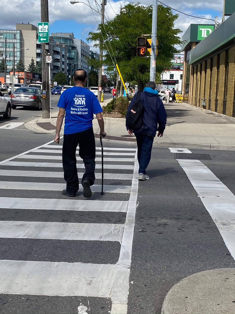 man with cane crossing multilanes of tra