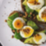 Nutritious meal of boiled eggs, avocado, and seeds on toast.