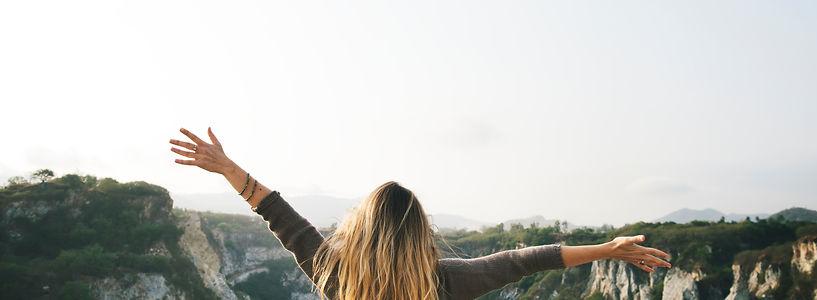 Femme bras ouverts devant une montagne
