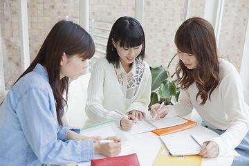 机を囲む女子学生
