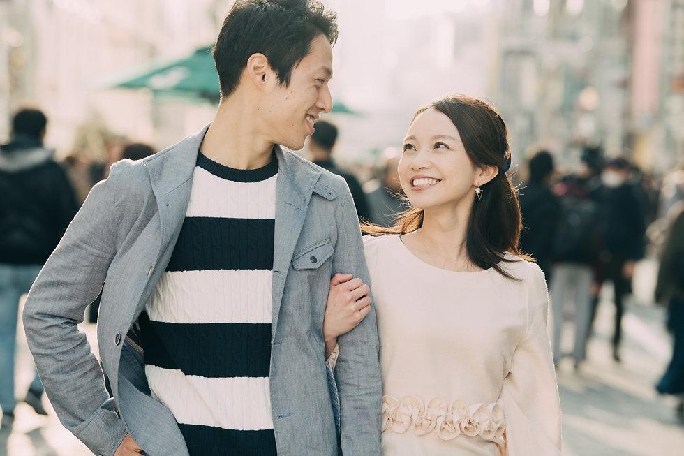 腕を組んで歩く若いカップル 笑顔