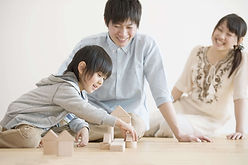 床であそぶ子供と家族