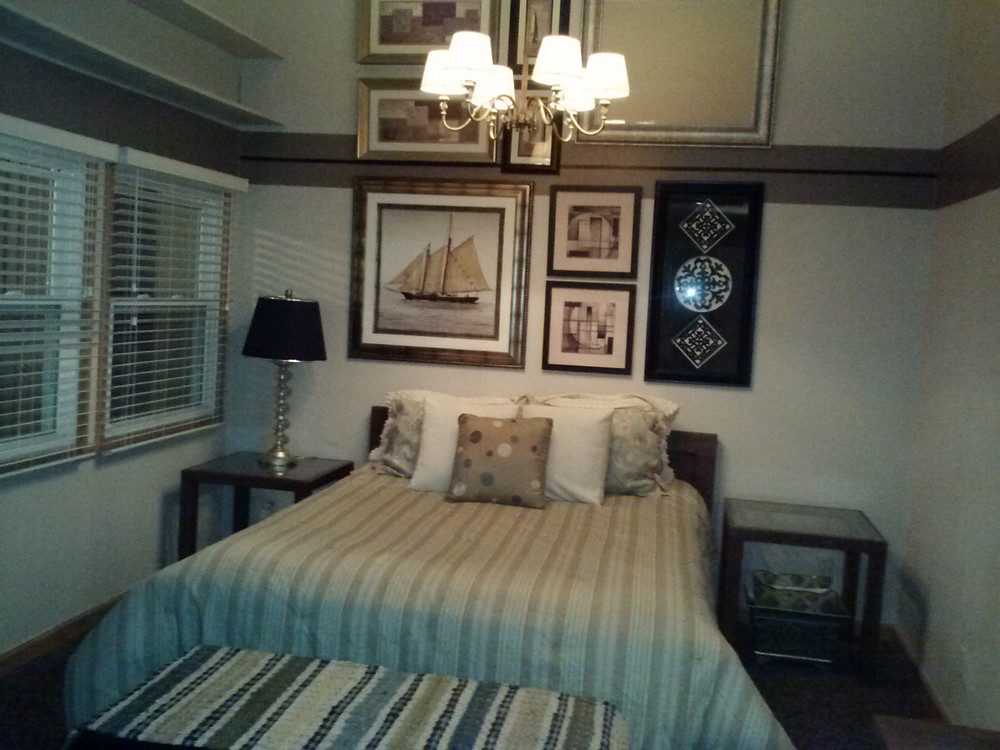 """Took this staged home to a budgetary """"other"""" place.   Set the bed the other direction, changed out the dated ceiling fan with a repurposed hanging fixture in front of a budget gallery wall to accentuate the tall ceilings.  Wouldn't you rather live here?"""