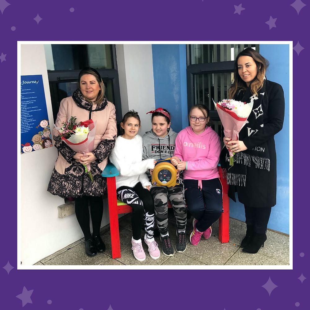 Committee members Janine and Caroline donating defibrillator to Clea Primary, Keady