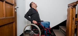 Cadeirante parado em frente a uma escadaria olhando para cima.