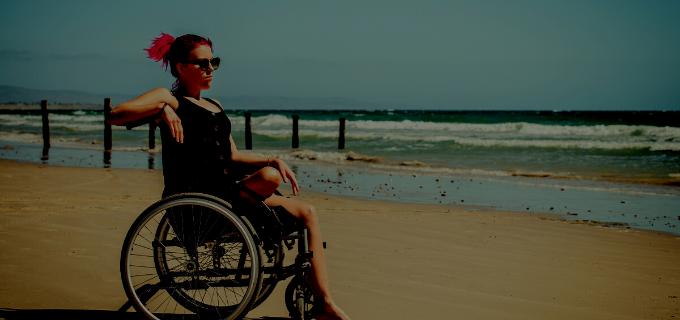 Mulher cadeirante na praia tomando sol