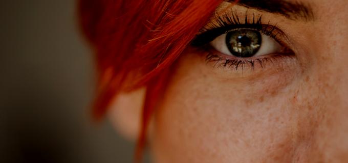 Metade do rosto de uma mulher ruiva com destaque em um dos olhos bem abertos
