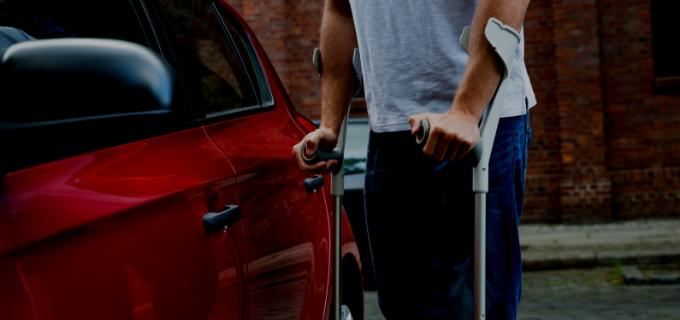 Homem de muletas indo em direção à porta de um carro.