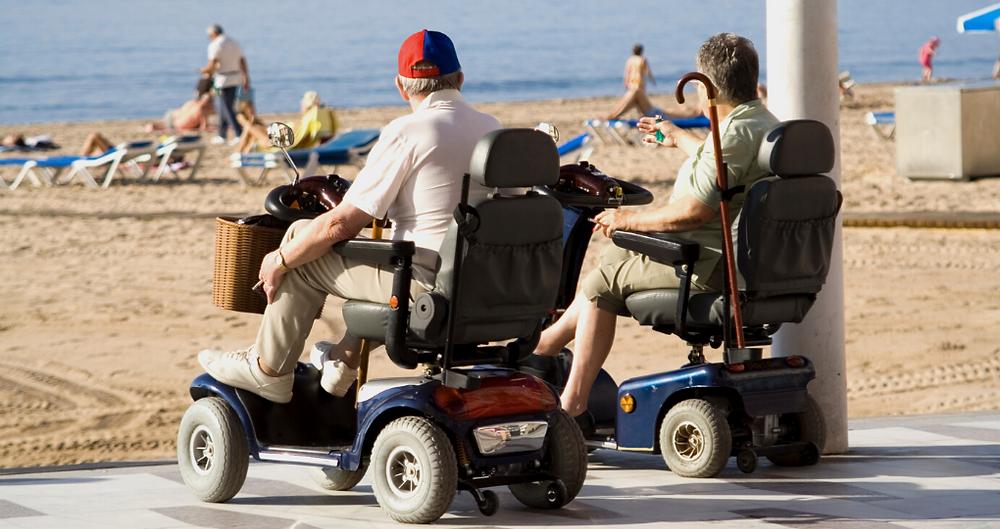 Dois homens em cadeira de rodas motorizada curtindo um sol à beira de uma praia.