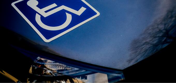 Imagem do capô de um carro com adesivo com símbolo da acessibilidade.