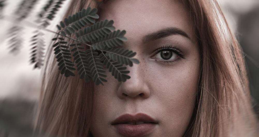 Rosto de uma mulher com semblante sério. Uma folha de planta está tampando um de seus olhos