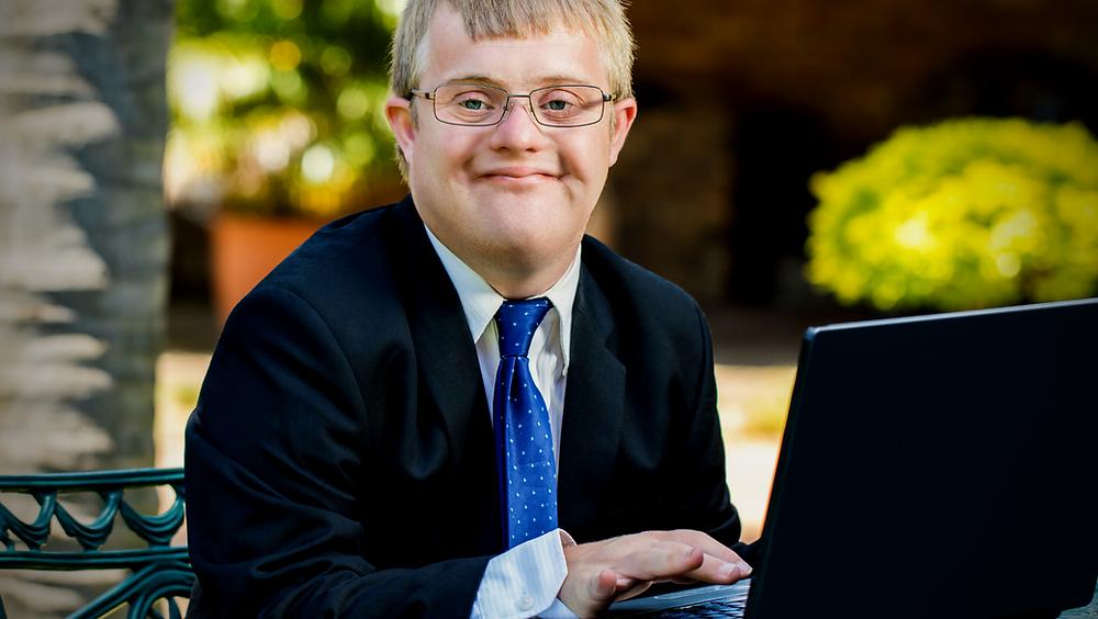 Jovem com síndrome de down trabalhando com notebook