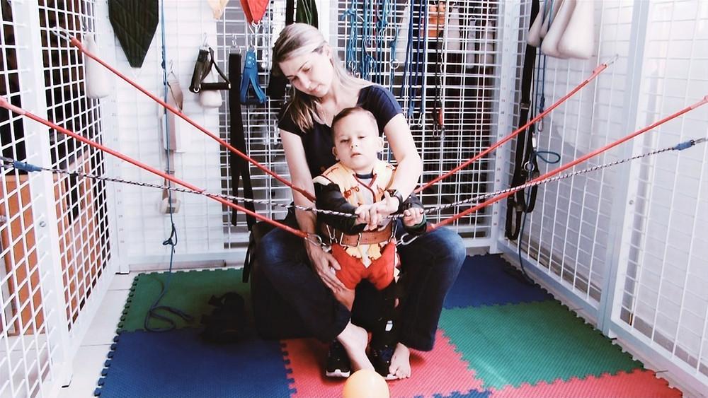 Criança com a veste TheraSuit junto com a fisioterapeuta em uma gaiola de reabilitação