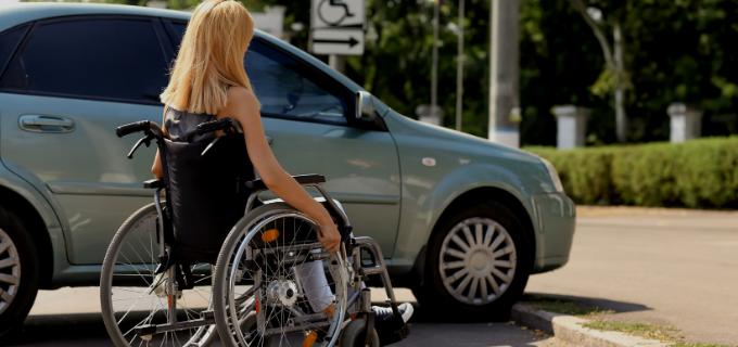 Mulher cadeirante parada em frente um carro próximo a uma calçada