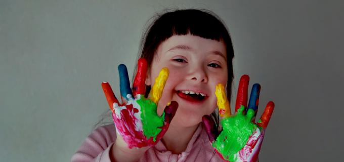 Garotinha autista sorrindo com as mãos abertas e pintada de várias cores