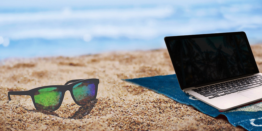 Sunglasses and laptop at the beach