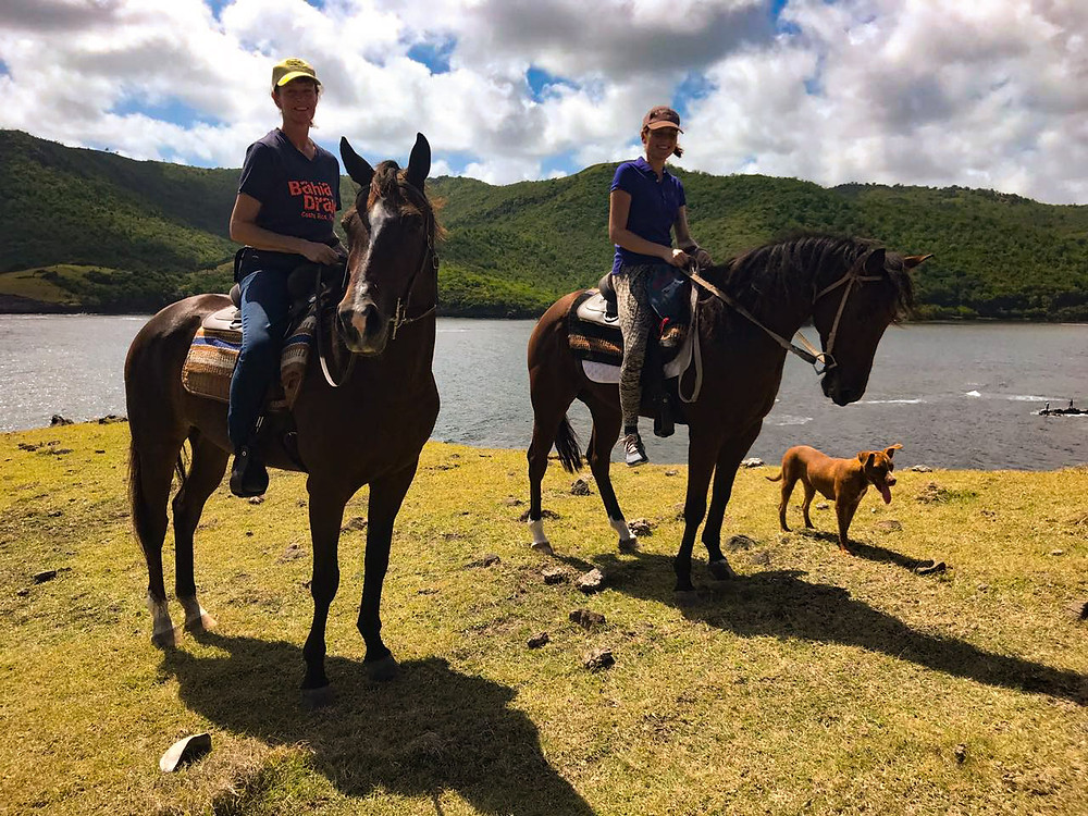 Two ladies horseback riding along the coast with Sandy Hoofs St. Lucia.