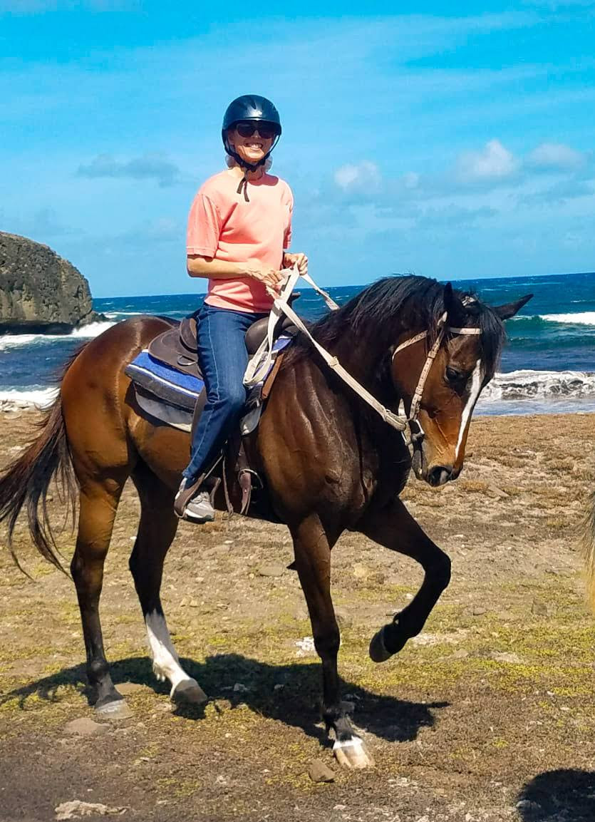 A lady horseback riding on the beach with Sandy Hoofs St. Lucia
