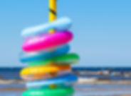 Stack of colorful inflatable swimming ri