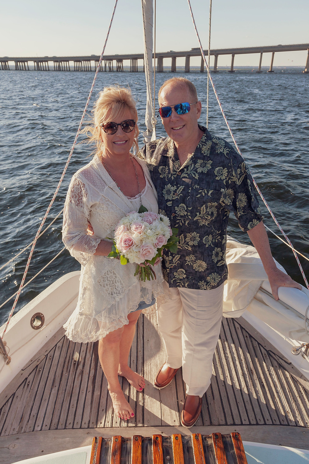 Newlywed couple poses after their ceremony aboard sailing vessel Selah with Fair Winds Sailing Co in Destin, Florida.