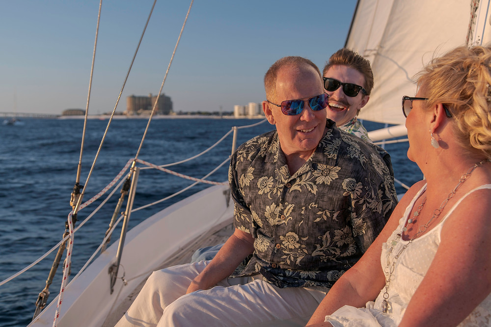 The wedding party enjoying a sail on the Gulf of Mexico as the sun sets over Destin, Florida.