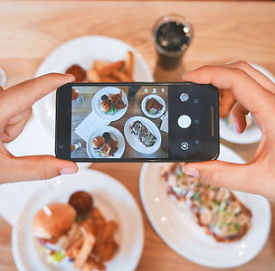 Online experiential marketing, someone taking a picture of a spread of food