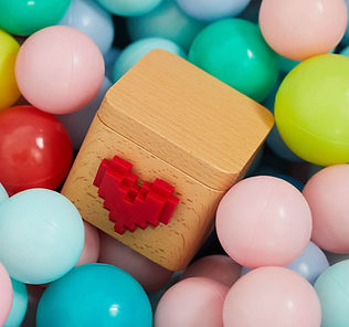 E-commerce copywriting, a wood box with a pixelated heart on it sitting amongst pastel colored balls