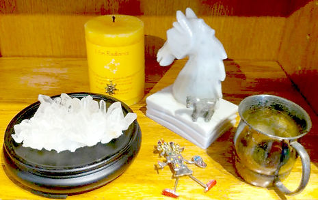 Image of an altar with a candle, quartz cluster, silver mug, and horse scultures