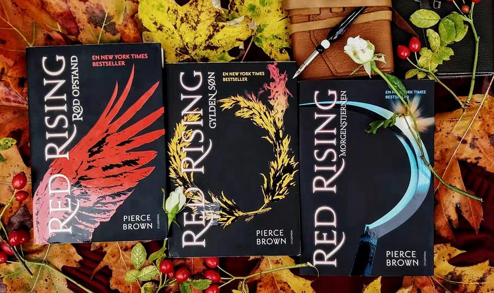 På billedet bogserien Red Rising skrevet af Pierce Brown. Bøgerne er omgivet af efterårsblade, blomster og notesbøger.