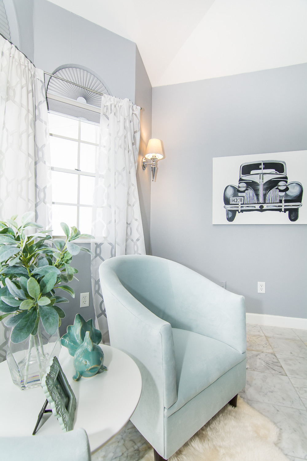 Pale blue accent chair in master bedroom sitting nook, gray walls